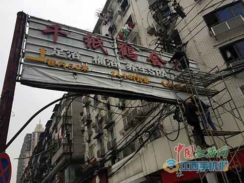 工作人员拆除存有安全隐患的广告牌。本报记者蔡颖辉摄