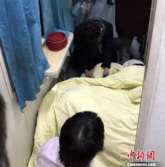 """图为列车工作人员和热心旅客在车厢里搭建临时""""产房"""",救治产妇和婴儿 李江 摄"""