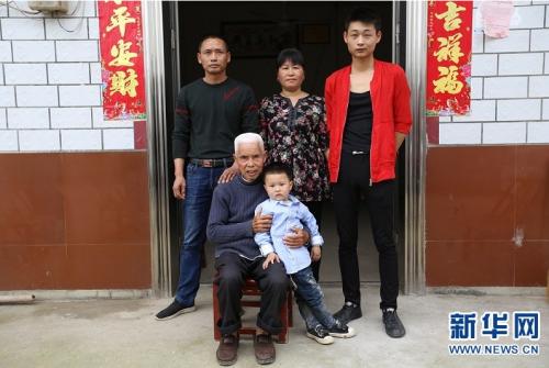 图为刘细根一家与老人刘周三(前排左一)合影。