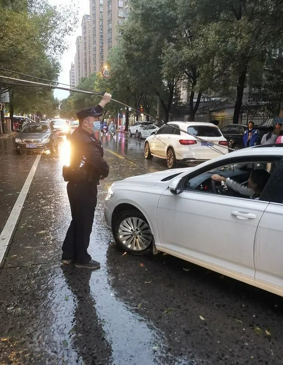 九江民警雨中托举电线1小时 附近市民陆续加入支援队伍