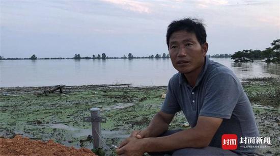 """双港镇双港村村支书彭俊英也一直坚守在抗洪一线,他说""""人在,堤在""""。他的家在水库下游,洪水水位线已经高过家里的房顶。"""