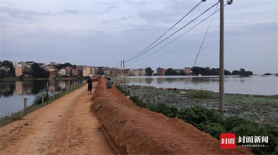 """7月12日晚饭时间,彭芳腊(左)和彭俊英(右)在守护的""""第二道防线""""堤坝上,吃了晚饭。 堤坝右侧是从鄱阳湖饶河流域漫过双峰南圩堤的洪水,淹没2万余亩农田。水位高过左侧水库,以及下游5个村庄。"""