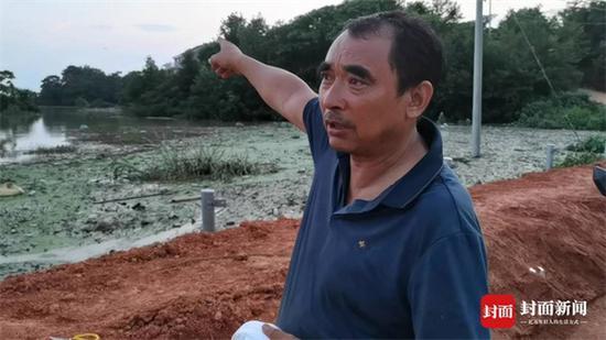 江西省鄱阳县双港镇双丰村村支书彭芳腊,向封面新闻记者讲述双峰南圩堤失守时,他带着官兵朝高处狂奔5公里的经过。 其身后是洪水漫过圩堤后,淹没了农田。