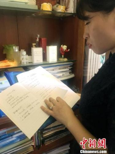 图为刘传健妻子邹函在家中翻阅丈夫的工作笔记。 刘贤 摄