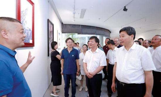 """7月17日,在三宝蓬艺术聚落,陈兴超、钟志生一行参观""""景漂之家""""成员画作。 (本报记者黄原珂摄)"""