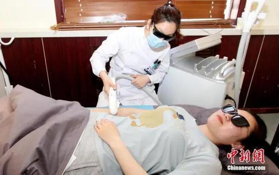 资料图:医师正在进行胳膊脱毛。中新社记者 张道正 摄