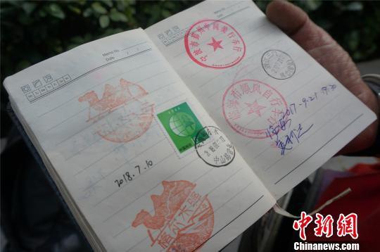 男子一年骑行万里宣传环保 本子上盖满全国邮戳