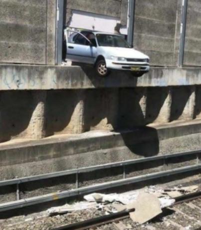 肇事车辆一半悬在铁轨上方摇摇欲坠。