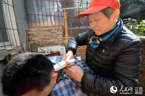 尽管不是专业理发师,但理发时,邹勤敏却非常认真仔细。