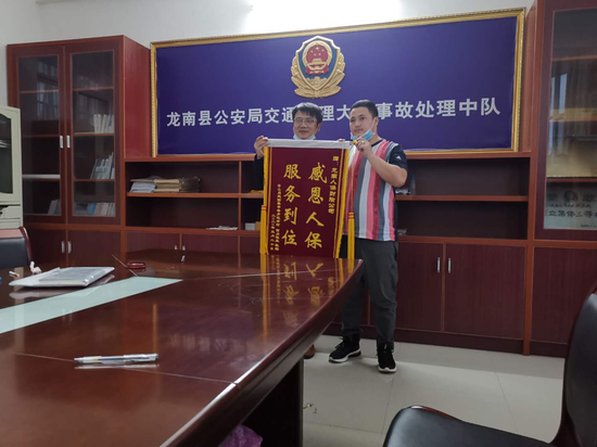 图为在龙南县公安交通处理大队,马海某某的家属将锦旗赠送给中国人保财险龙南支公司工作人员。(沟通全程配戴口罩,图中为合影人员应拍照要求,暂时脱下口罩。)