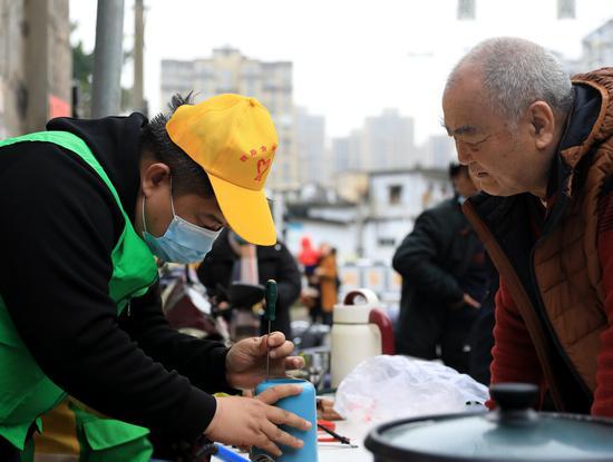 南铁志愿者为居民免费维修豆浆机。摄影:王福斌