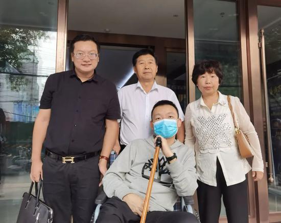 姚策坐在轮椅上和亲生父母及律师合影。受访者供图