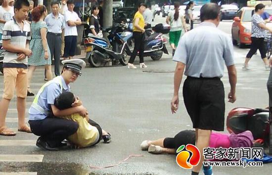 8月17日在车祸现场,刁志强一直蹲着救护伤者。这张照片在朋友圈广泛传播。