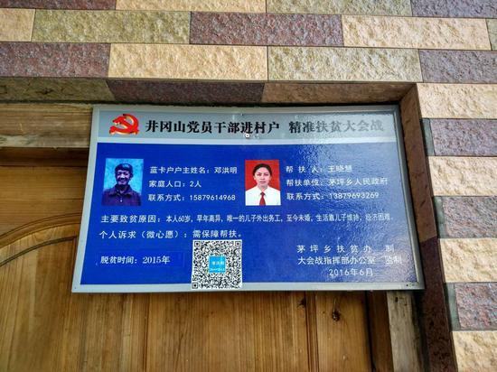 邓洪明家墙上的定点帮扶卡