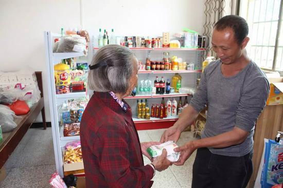前来兑换商品的朱华清老人(左一)和李玉华(右一)