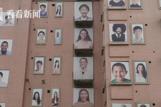 大楼外墙挂百幅笑脸图 路人吐槽:晚上看瘆得慌