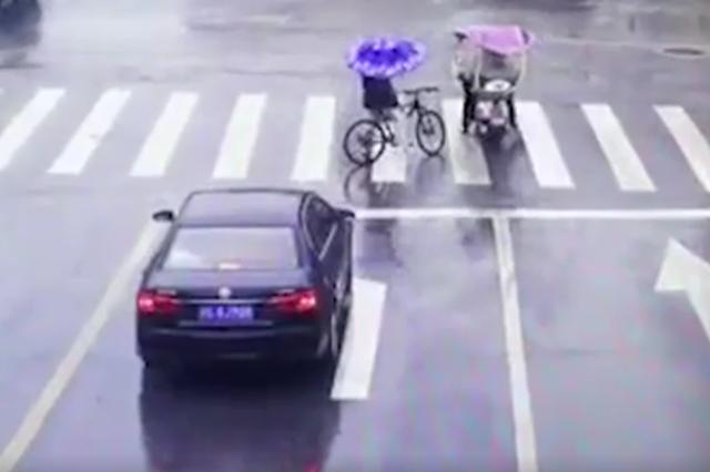 暖!上高守交规女孩淋雨等绿灯 同行路人递上一把伞