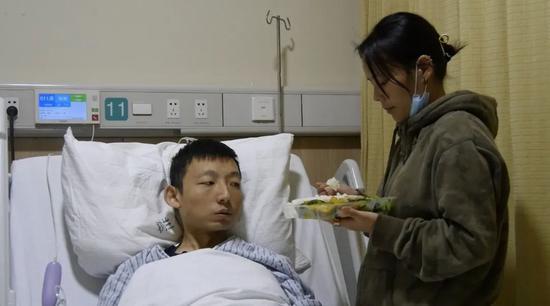 姚策妻子在给躺在病床上的姚策喂饭。新京报记者 刘名洋 摄