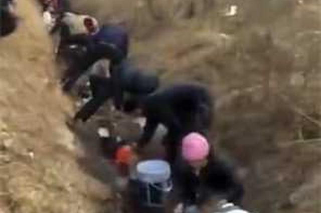 高速油料泄露流地沟 村民开三轮车拎桶盆争相打捞