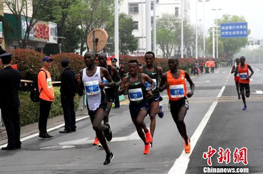 图为参赛的高水平专业马拉松运动员始终跑在队伍前面的第一方阵。 崔佳明 摄