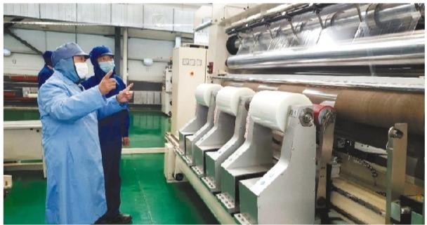 销售部经理陈建伟(左)在第三条生产线车间向记者介绍产品生产情况。