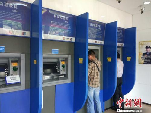 资料图:民众在自动取款机上取钱。记者 李金磊 摄