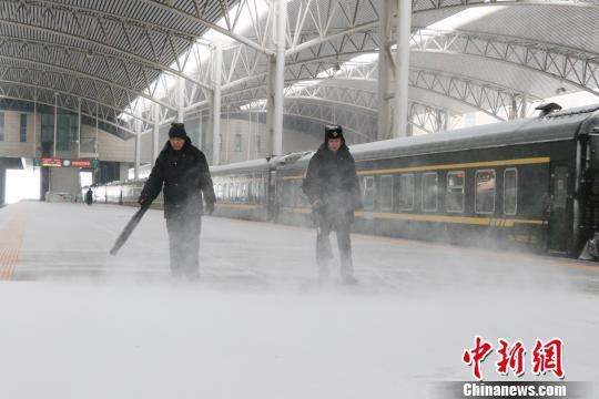 工作人员在站台除雪,确保旅客乘降安全。 钟欣 摄