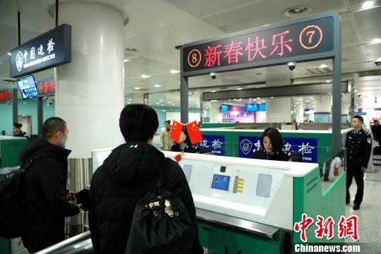 """边检验证台显示屏显示""""新春快乐""""字样欢迎旅客回家 王景巍 摄"""