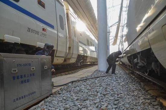 上水作业人员使用智能客车上水栓,为停靠动车组列车进行上水