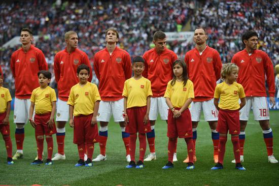 来自中国山东青岛的张瀚(前排右三)和俄罗斯队员一起站在开幕赛的绿茵场上