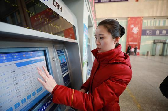 张允帮助旅客在自动售票机上购买车票 王强摄