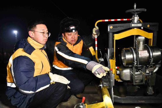 工长陈金贵指导青年职工使用机械设备