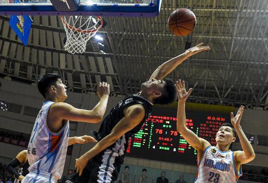 ↑4月14日,辽宁本钢队球员李晓旭(中)在比赛中与新疆广汇汽车队球员俞长栋(左)拼抢。