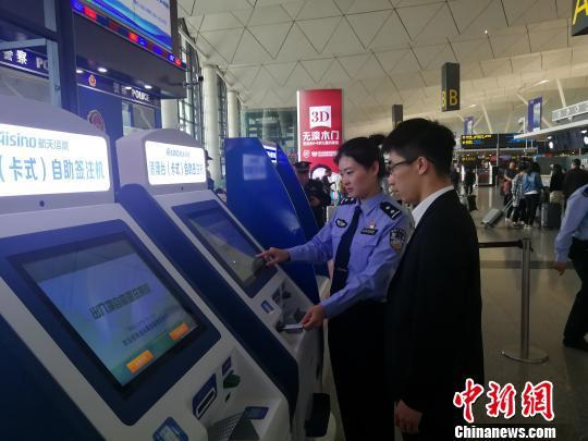 """民警正在指导旅客操作""""自助签注机""""办理签注业务。 王景巍 摄"""