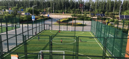 市民在室外笼式足球场踢球。