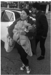 家人抱着烫伤婴儿下车。
