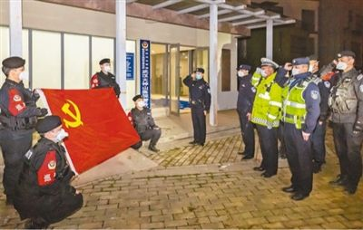 2月1日,武汉市火神山医院警务室挂牌成立。当晚,警务室组建了8人组成的党员突击队,成员们在党旗前宣誓。   本报记者 张武军摄