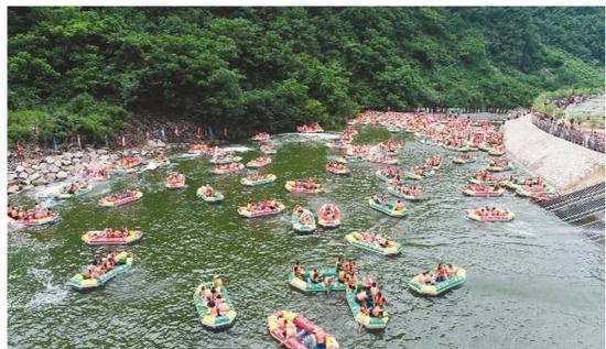 图为游客在大连庄河云水谷中进行漂流体验。