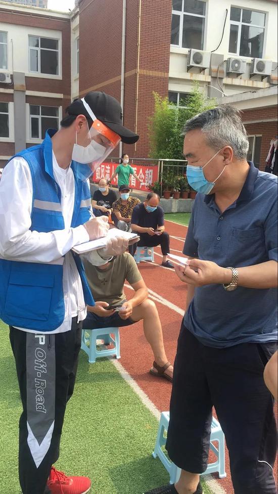 多军英的儿子(左)在为社区居民登记信息