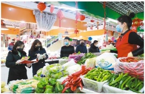 """我省市场监管人员在农贸市场进行检查,保障居民""""菜篮子""""安全。"""