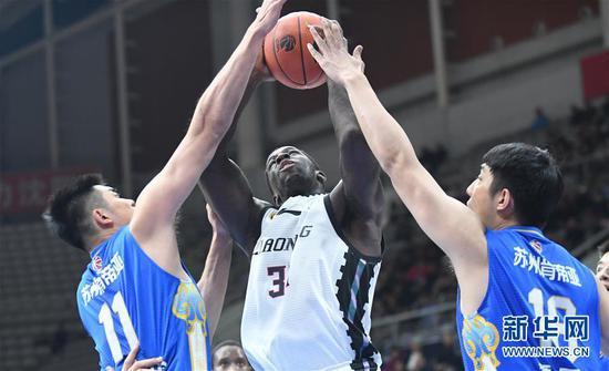 12月9日,辽宁本钢队球员巴斯(中)在比赛中投篮。新华社记者龙雷摄