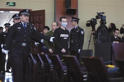 昨日,海淀法院开庭审理获取4000余万条公民信息助考诈骗案,被告人曾爱国(戴口罩者)等14名被告人被带入法庭。 新京报记者 王飞 摄