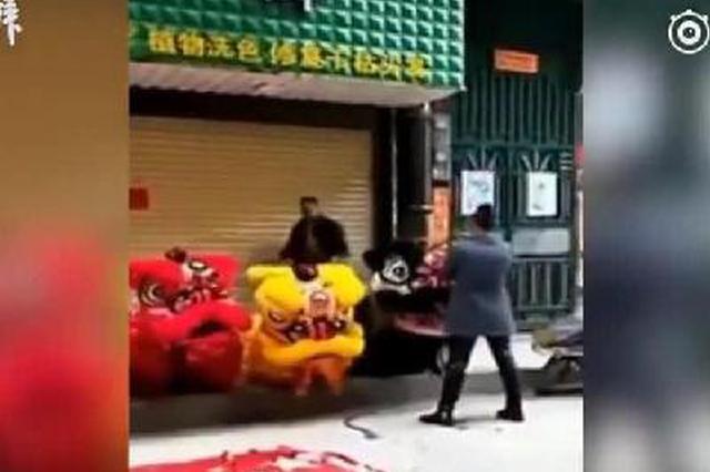 实拍:舞狮表演过程中 男子用国旗摆祭品并踩踏
