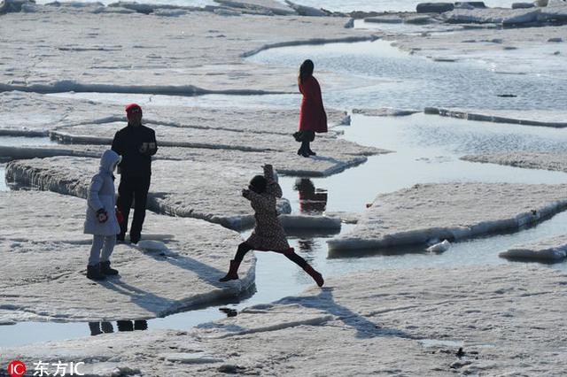 大连渤海海冰融化 游客浮冰上跨大步不亦乐乎