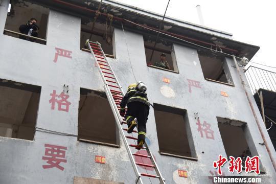 消防官兵用拉梯登上4层大楼。 王以照 摄