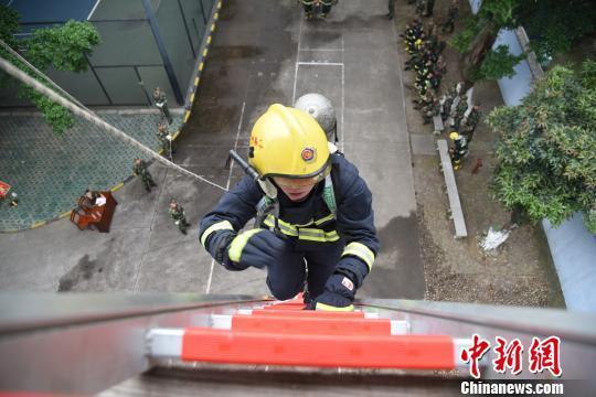 消防官兵正在攀爬拉梯。 王以照 摄