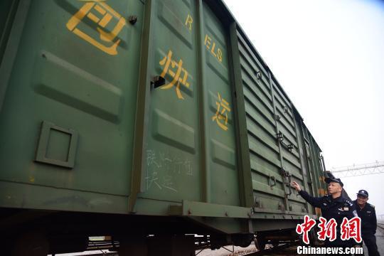 唐楚伟和辅警对货运车厢锁具进行检查。 王以照 摄