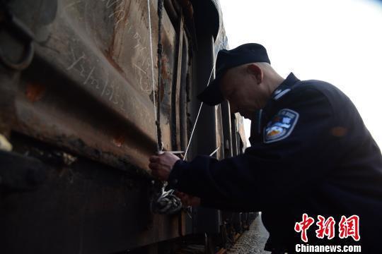 唐楚伟正在检查车货运厢的扎带。 王以照 摄