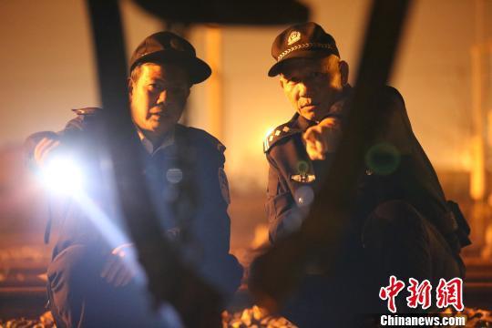 夜幕降临,唐楚伟和辅警在线路中巡查。 王荣鑫 摄