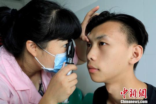 一名医生在为大学生检查眼睛。 谭凯兴 摄